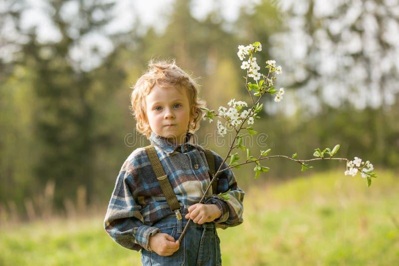 摆在开花的果树园的年轻白肤金发的男孩春天 免版税库存照片