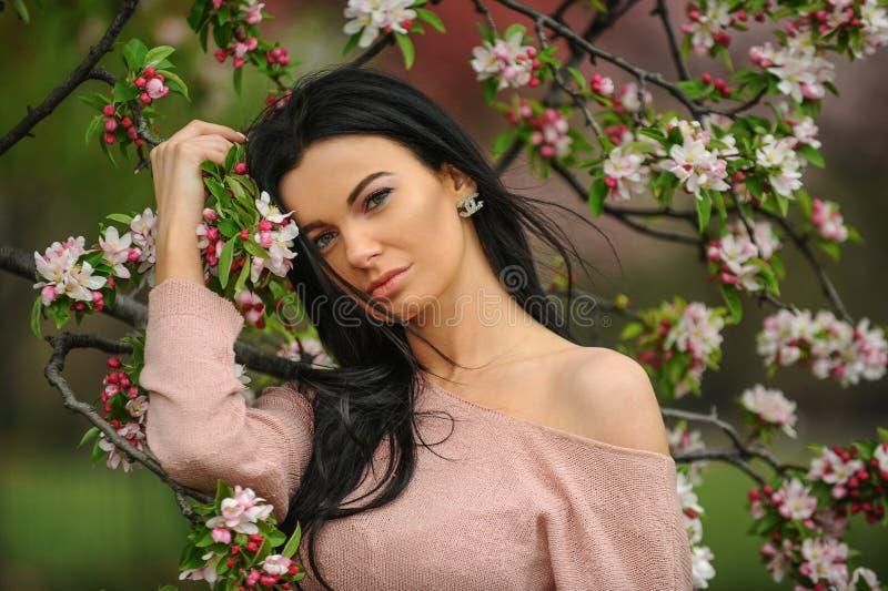 摆在开花的树附近的年轻美丽的时兴的夫人室外画象  库存图片