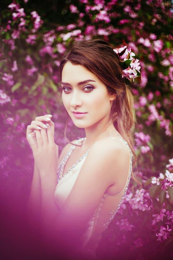 摆在开花的苹果树中的年轻美丽的妇女画象  库存照片