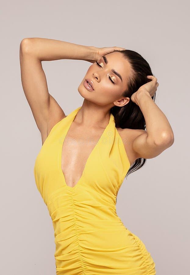 摆在微型黄色礼服的肉欲的夫人 免版税图库摄影