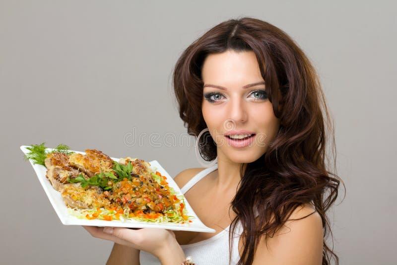 摆在微笑的妇女年轻人的膳食 免版税库存照片