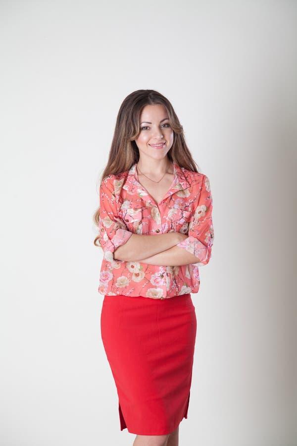 摆在微笑的桃红色西装的女孩 免版税库存图片