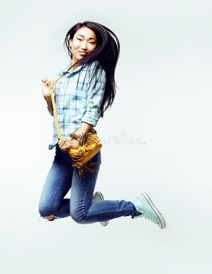 摆在快乐情感的年轻俏丽的跳跃的亚裔妇女隔绝在白色背景,生活方式人概念 免版税库存图片