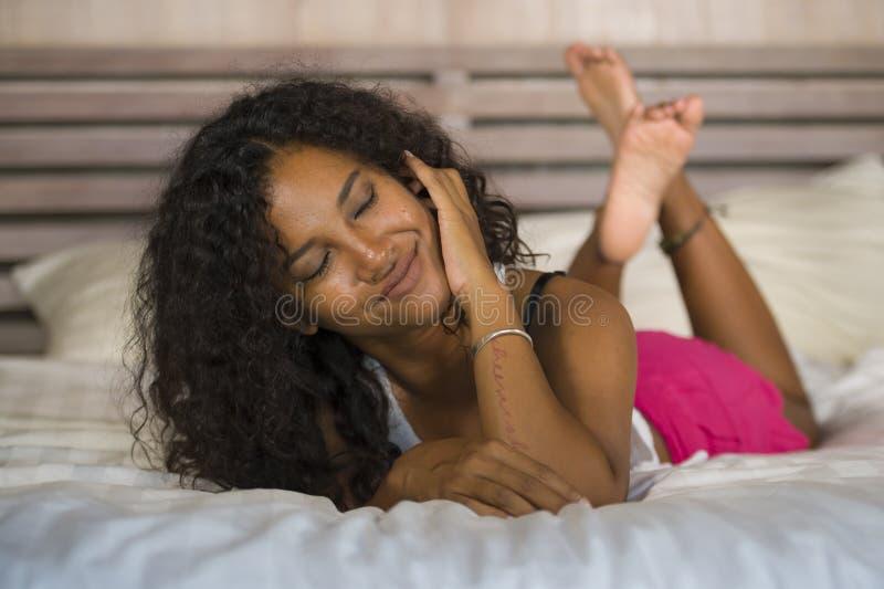 摆在性感和嬉戏卧室说谎的年轻愉快和华美的黑人拉丁美洲的妇女生活方式画象在家放松了  免版税库存照片