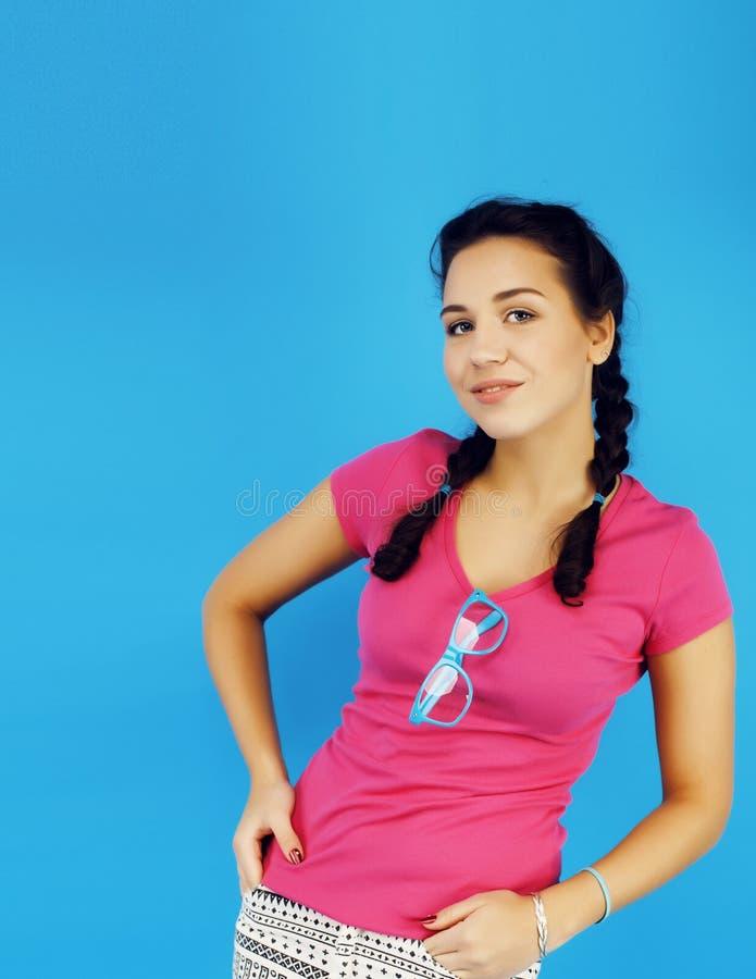 摆在情感愉快微笑在蓝色背景,生活方式人概念的年轻人相当少年现代行家女孩 免版税库存照片