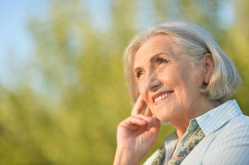 摆在愉快的美丽的年长的妇女画象户外 免版税图库摄影