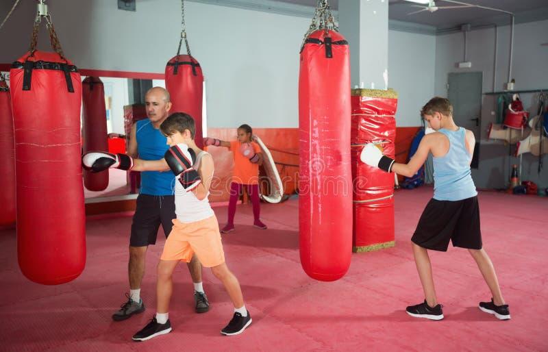 摆在战斗的姿态的少年在拳击健身房 库存图片
