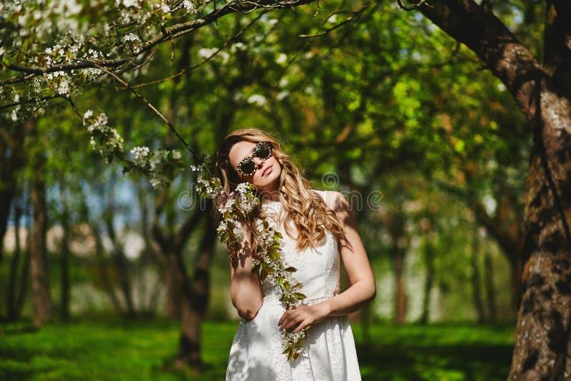 摆在户外在公园的白色礼服的美丽和时兴的年轻白肤金发的妇女 免版税库存图片