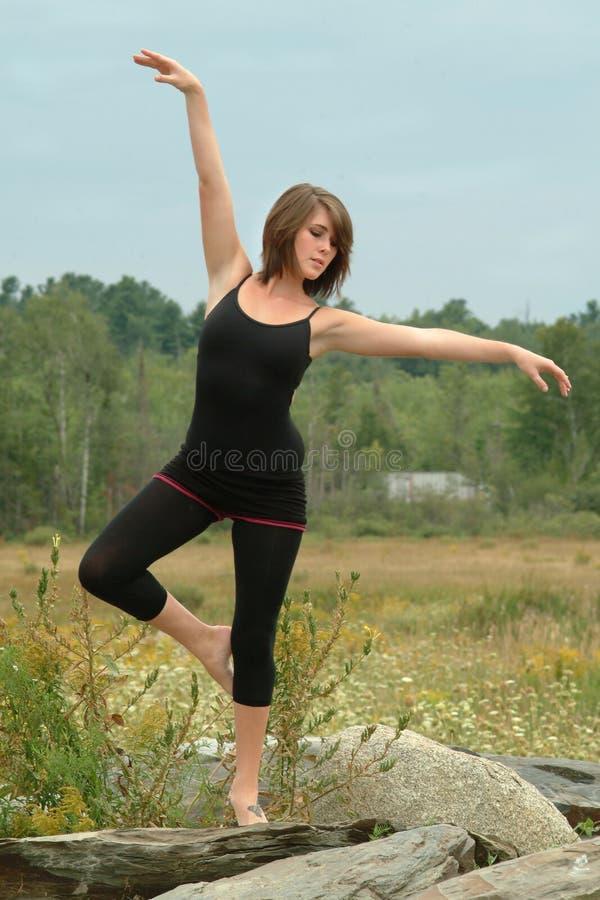 摆在户外在岩石的美丽的传神女性舞蹈家 库存图片