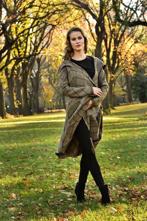 摆在户外在秋天公园的年轻美丽的俏丽的女孩全长画象  免版税库存照片