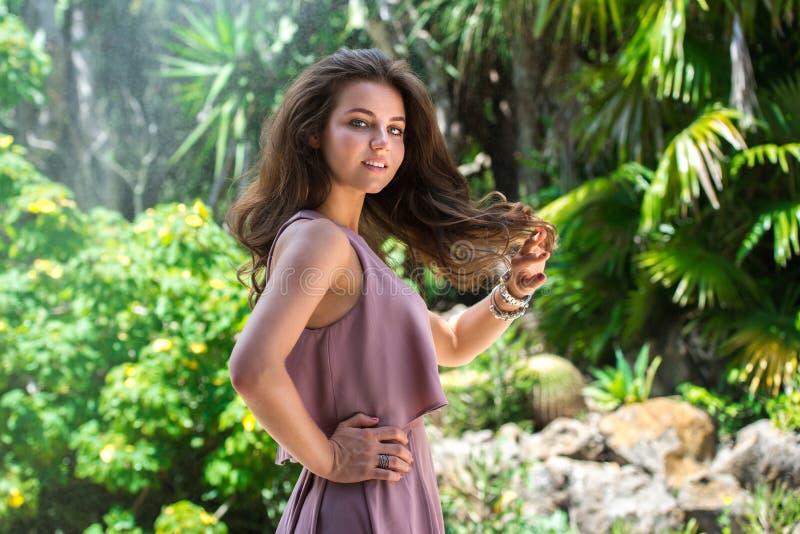 摆在户外在绿色热带森林背景的美丽的端庄的妇女 图库摄影