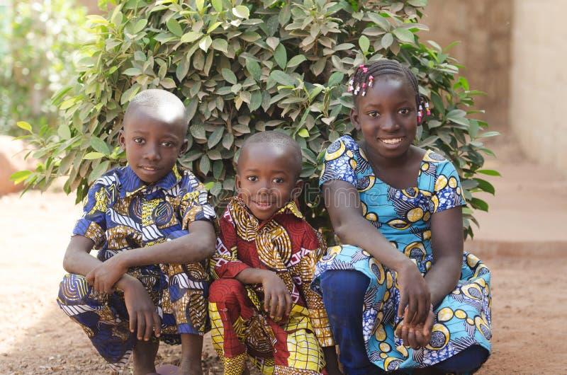 摆在户外微笑和Laug的三个华美的非洲孩子 库存照片