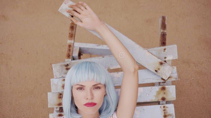 摆在损坏的木蓝色的现代未来派样式的性感的美丽的妇女sunbed 库存照片