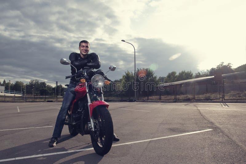 摆在摩托车的骑自行车的人 库存图片