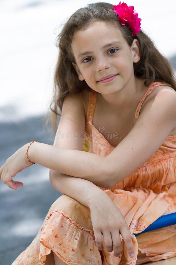 摆在操场的逗人喜爱的小女孩 免版税库存照片