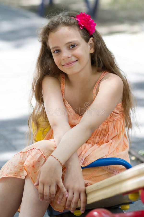 摆在操场的逗人喜爱的小女孩 免版税图库摄影