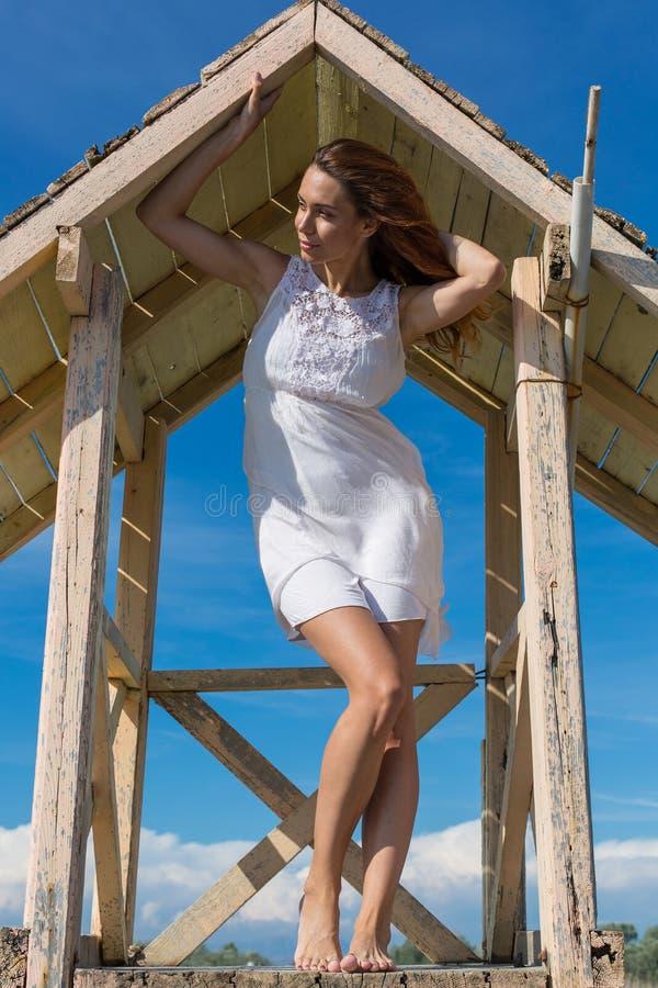 摆在救生员塔的年轻可爱的女孩 免版税库存图片