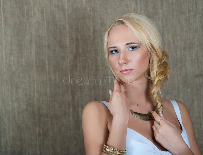 摆在斯拉夫的种族首饰的一个年轻白肤金发的女孩的画象 免版税库存照片