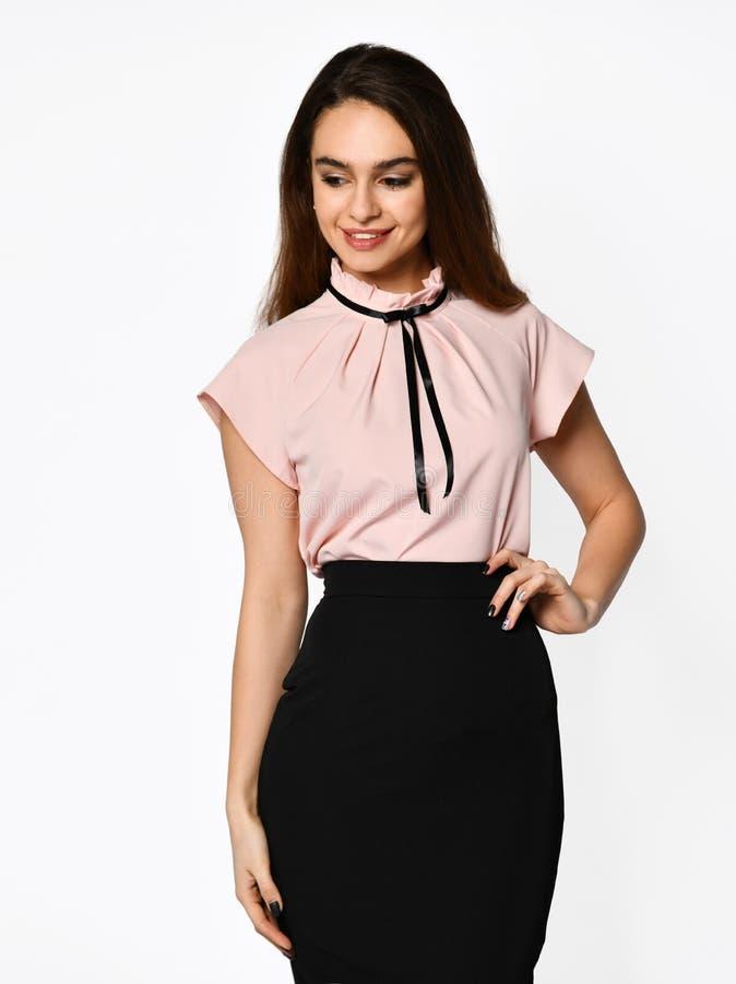 摆在新的偶然在灰色的办公室布料温暖的桃红色衬衣的年轻美女 库存照片