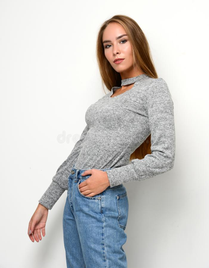 摆在新的时尚蓝色牛仔裤和套头衫的年轻愉快的美丽的妇女 库存照片