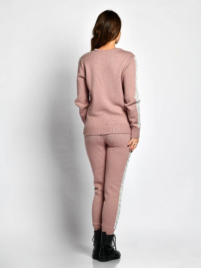 摆在新的浅粉红色的时尚冬天被编织的衣服充分的身体后部的年轻美女从后面 免版税库存图片