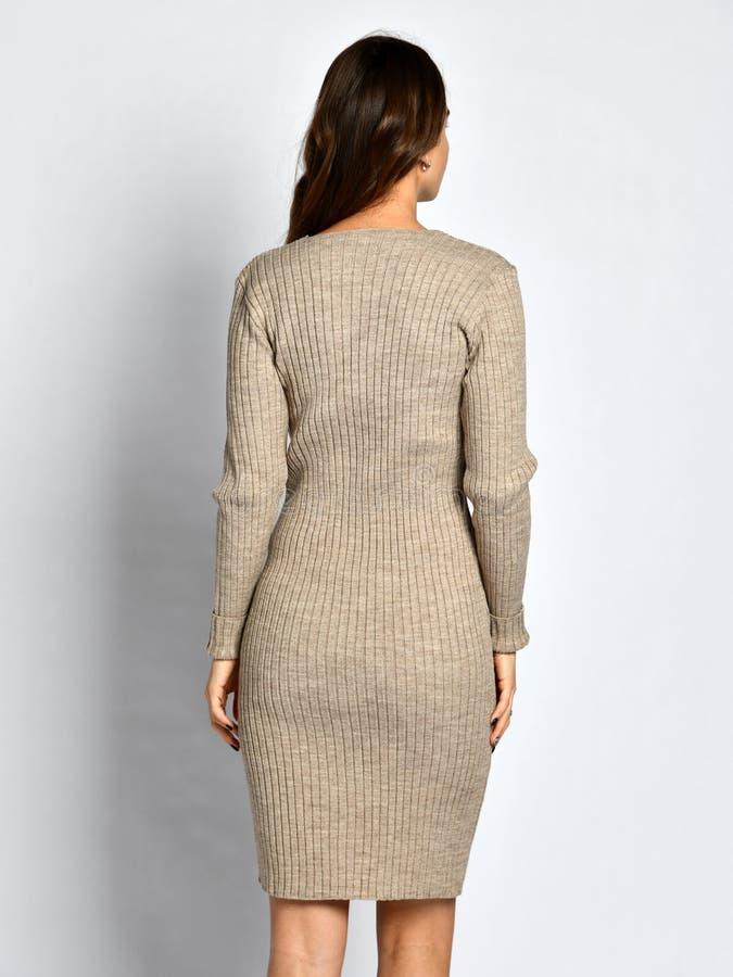 摆在新的灰色时尚冬天被编织的礼服后部的年轻美女从后面 免版税库存照片