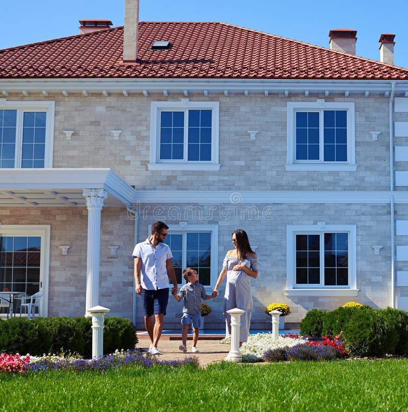 摆在新的现代房子前面的愉快的家庭 库存照片