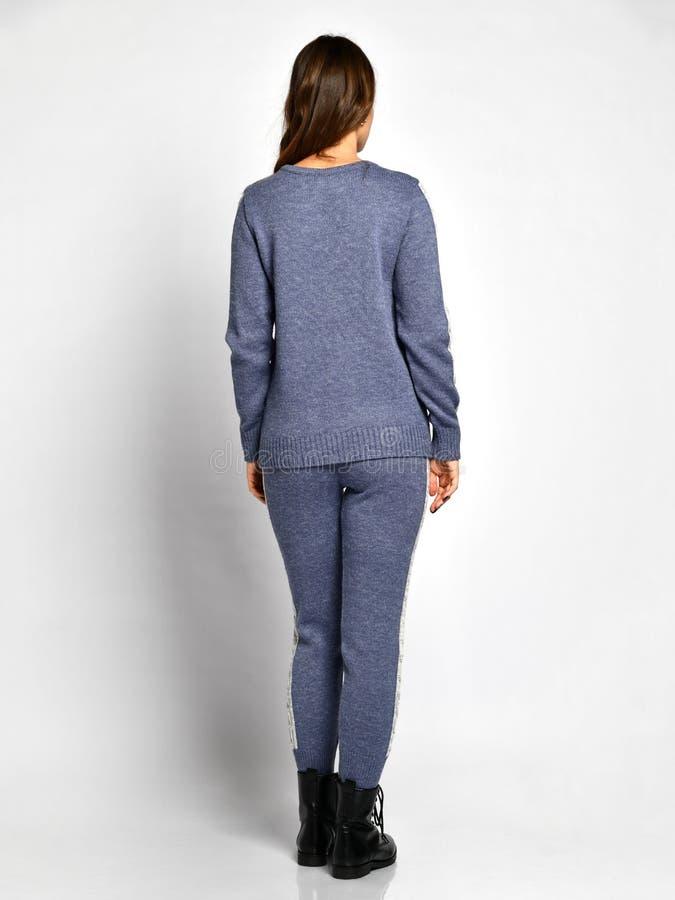 摆在新的蓝色时尚冬天被编织的衣服充分的身体后部的年轻美女从后面 库存照片