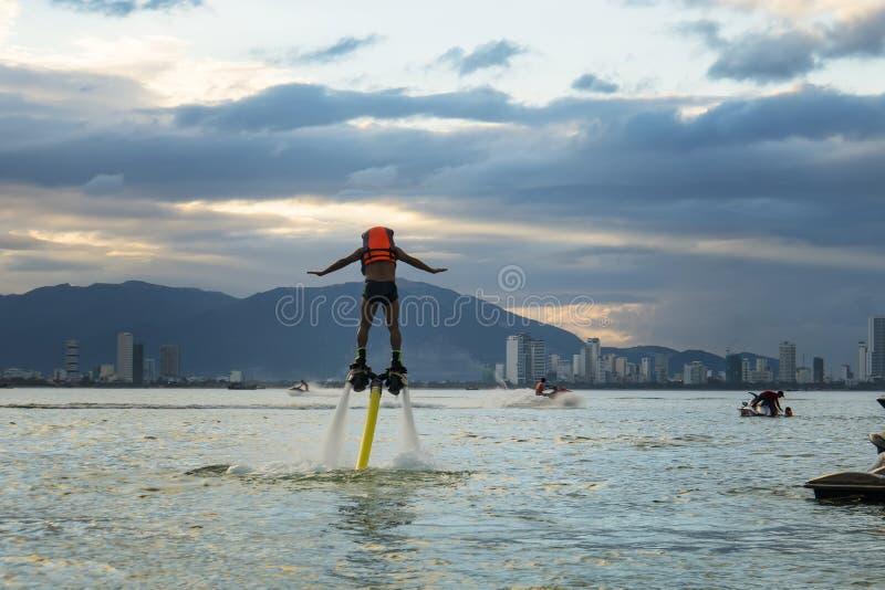 摆在新的flyboard的人在热带海滩在日落 正面人的情感,感觉,喜悦 做假期的滑稽的逗人喜爱的人 图库摄影