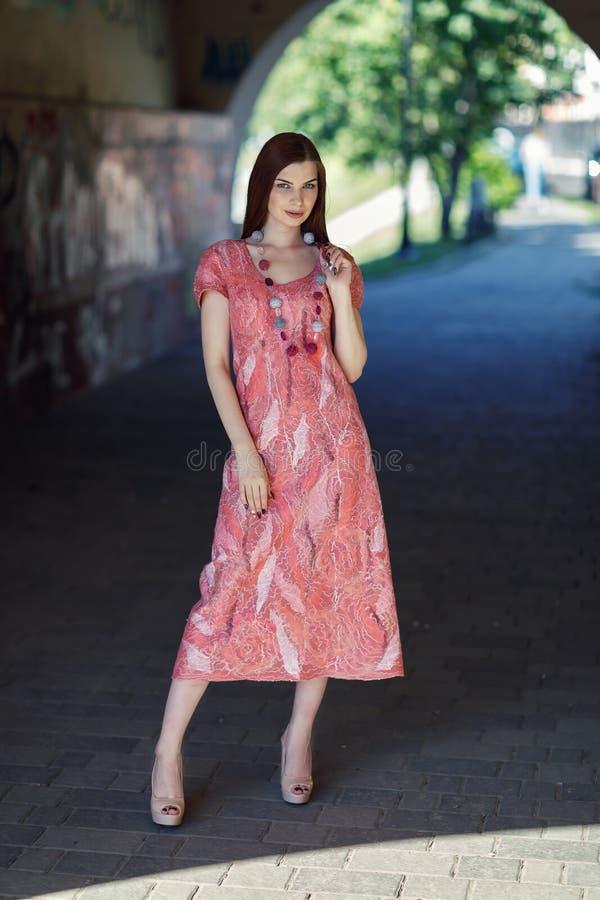 摆在无缝的礼服的年轻时髦的女孩 图库摄影