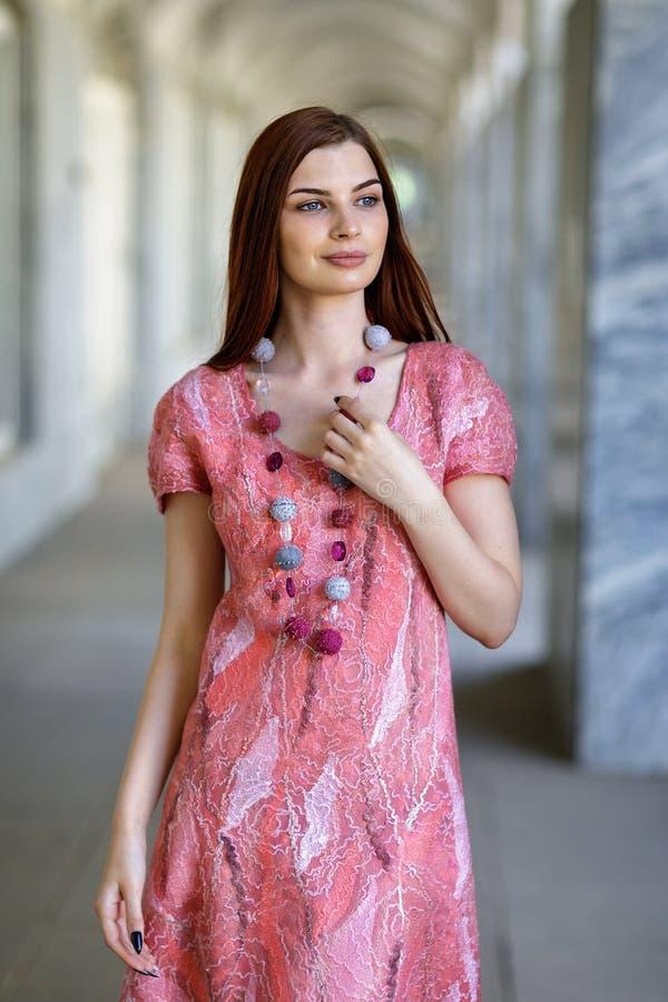 摆在无缝的礼服的年轻美丽的女孩做在作者` s t 免版税库存照片