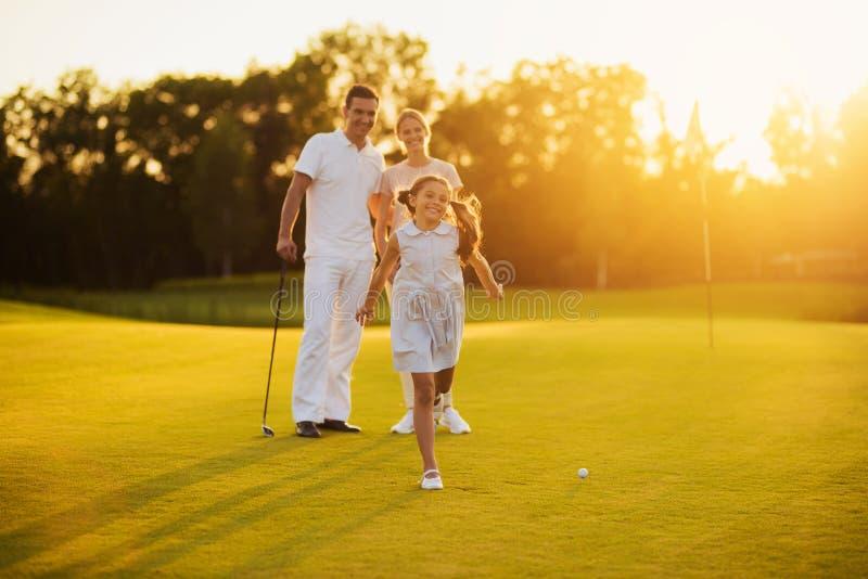 摆在日落背景的一个高尔夫球场的愉快的家庭 女孩微笑并且跑往照相机 库存图片
