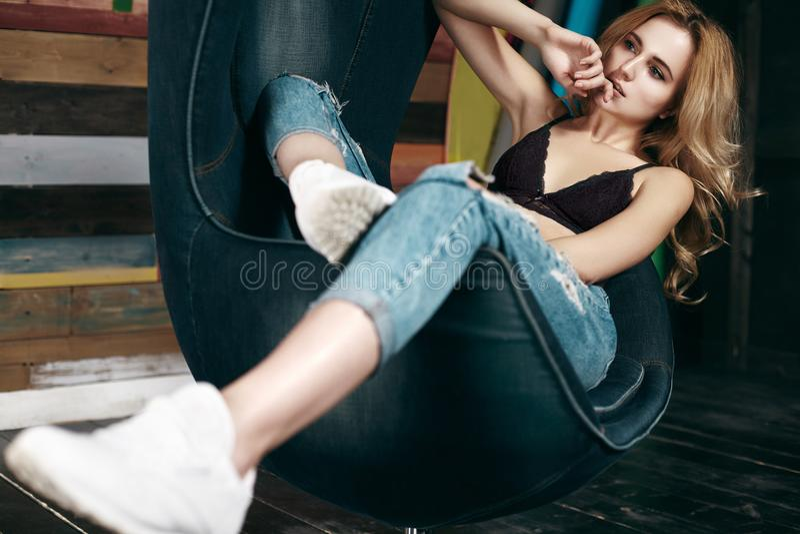 摆在时尚牛仔裤,白色运动鞋的美丽的少妇 有白肤金发的卷发的魅力女孩是松弛在椅子 免版税库存图片