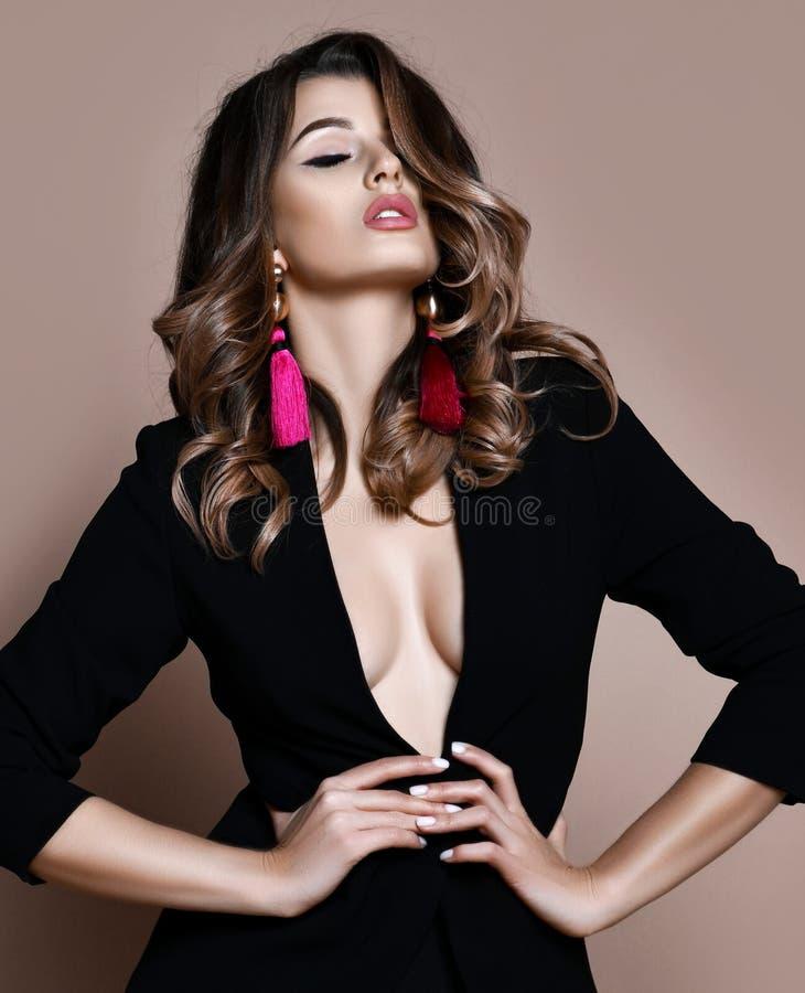 摆在时尚黑夹克的年轻肉欲的美丽的性感的妇女赤裸在温暖的灰棕色 免版税图库摄影