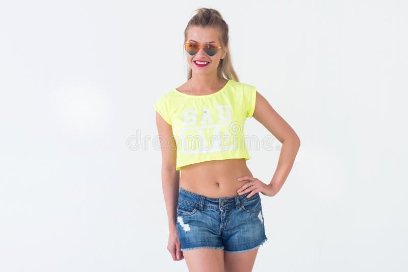 摆在时髦夏天成套装备,佩带的明亮的黄色T恤杉,太阳镜的美好的模型正面图画象 库存图片