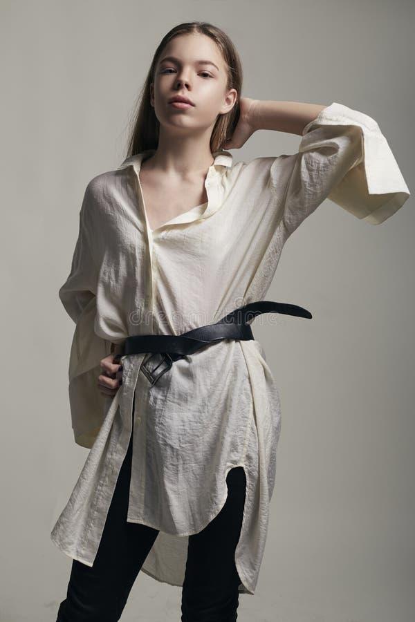 摆在时髦的衣物的演播室的年轻时装模特儿十几岁的女孩 便装样式,秀丽辅助部件,白色衬衫 免版税库存图片