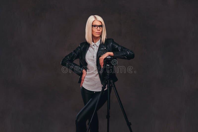 摆在时髦的衣裳的聪明的白肤金发的女性摄影师,当倾斜在与三脚架的一台专业照相机在a时 免版税库存照片