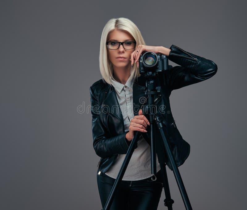 摆在时髦的衣裳的聪明的白肤金发的女性摄影师,当倾斜在与三脚架的一台专业照相机在a时 图库摄影