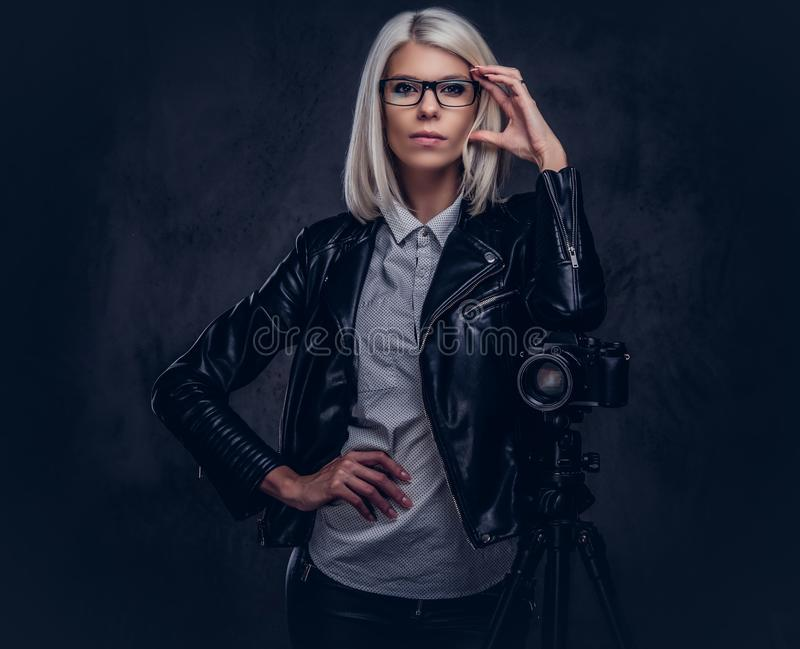 摆在时髦的衣裳的聪明的白肤金发的女性摄影师,当倾斜在与三脚架的一台专业照相机在a时 库存图片