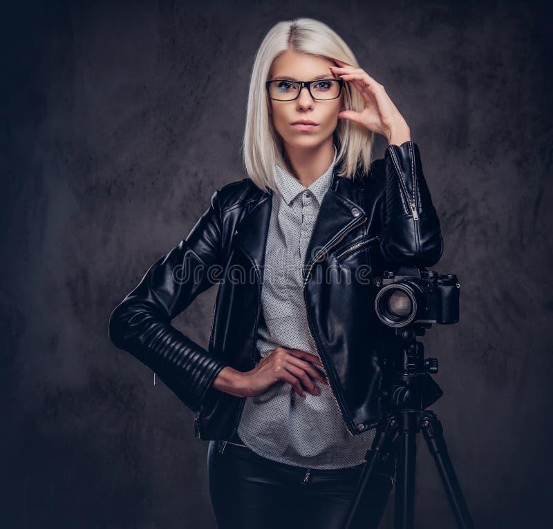 摆在时髦的衣裳的聪明的白肤金发的女性摄影师,当倾斜在与三脚架的一台专业照相机在a时 免版税库存图片