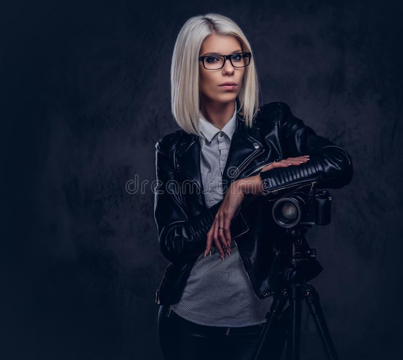 摆在时髦的衣裳的聪明的白肤金发的女性摄影师,当倾斜在与三脚架的一台专业照相机在a时 免版税图库摄影