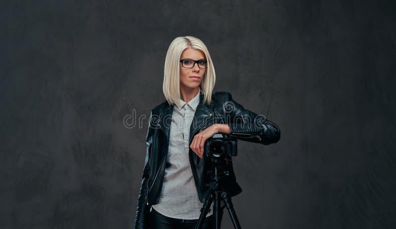 摆在时髦的衣裳的聪明的白肤金发的女性摄影师,当倾斜在与三脚架的一台专业照相机在a时 库存照片