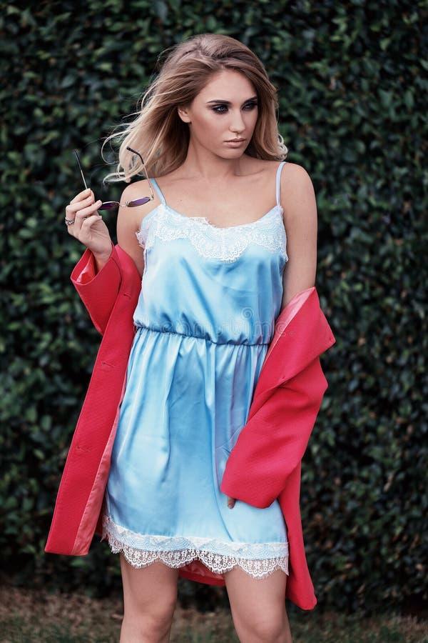摆在时髦礼服的美丽的时髦的年轻白肤金发的女孩 免版税图库摄影