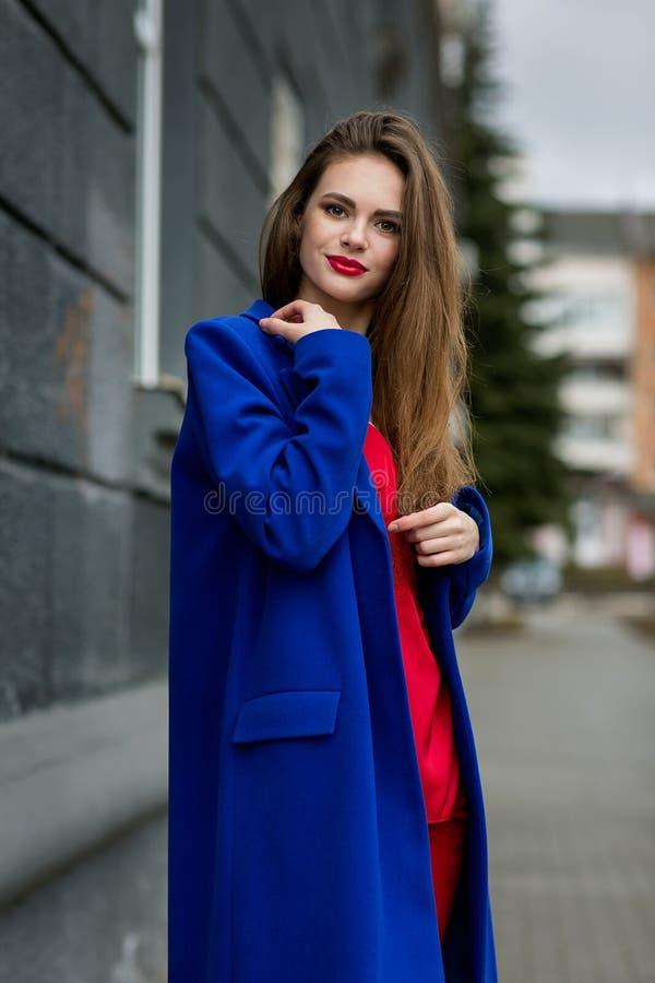 摆在时髦衣裳的年轻美丽的女孩 免版税图库摄影