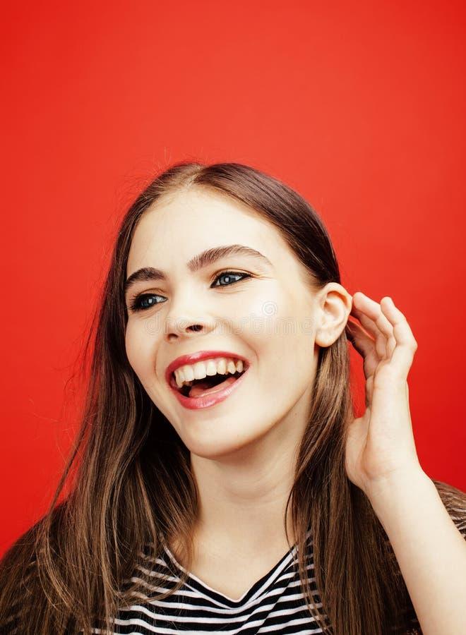 摆在明亮的红色背景的,愉快的微笑的生活方式人概念的年轻俏丽的emitonal十几岁的女孩 库存图片