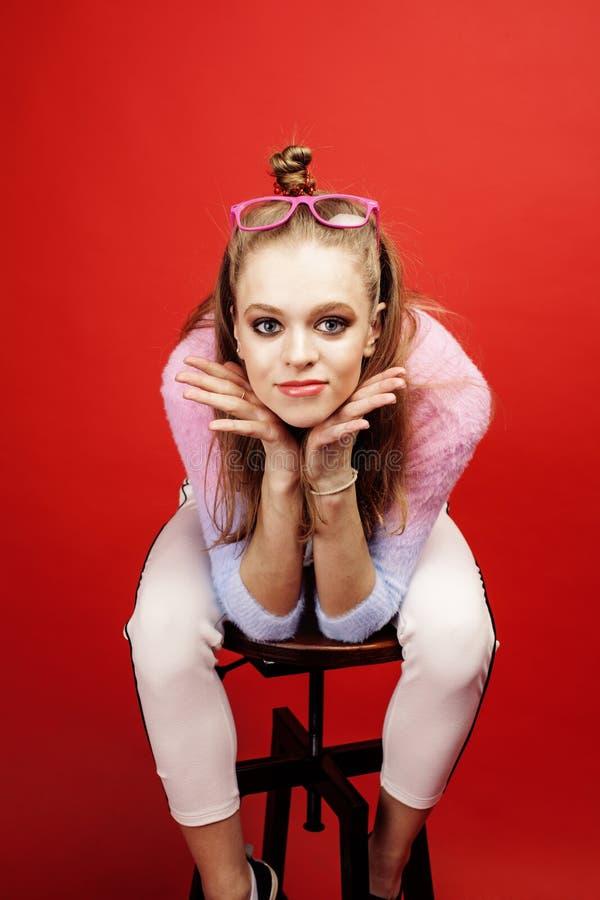 摆在明亮的红色背景的,愉快的微笑的生活方式人概念的年轻俏丽的emitonal十几岁的女孩 图库摄影