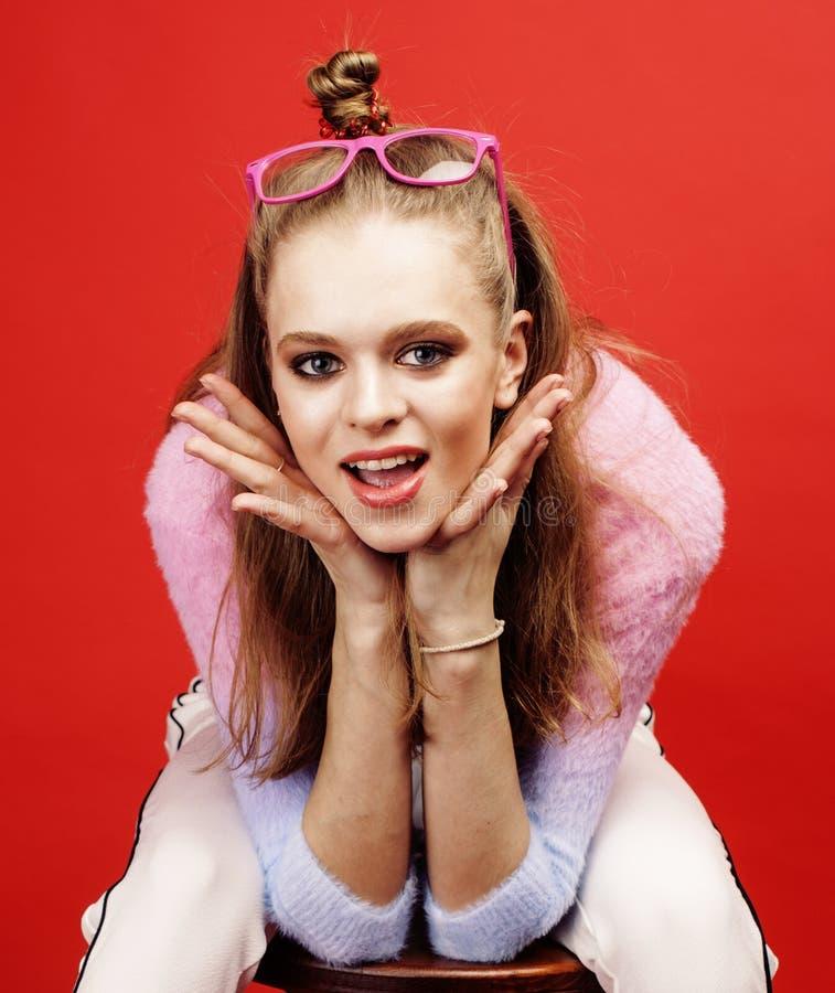 摆在明亮的红色背景的,愉快的微笑的生活方式人概念的年轻俏丽的emitonal十几岁的女孩 免版税库存照片