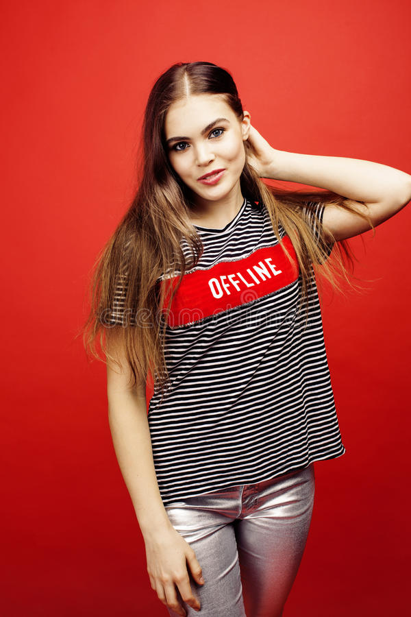 摆在明亮的红色背景的,愉快的微笑的生活方式人概念的年轻俏丽的emitonal十几岁的女孩 免版税图库摄影