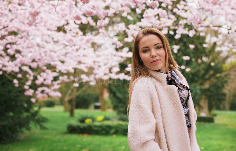 摆在春天庭院的美丽的少妇 免版税图库摄影