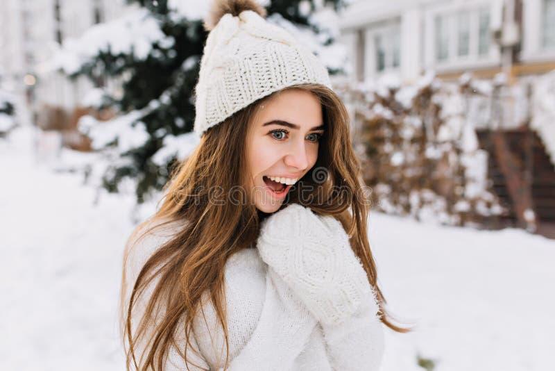 摆在有惊奇的微笑的多雪的街道的时髦的白色帽子的悦目女孩 可爱的欧洲少女与 免版税库存图片